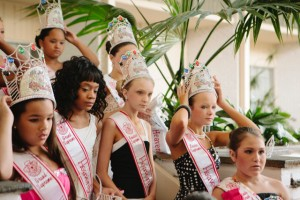 Emily, 11, poses for a photo with her fellow competitors. Emily is not pleased with the outcome of this pageant-- she had hoped to get a higher title. Emily Dextraze is an eleven-year-old beauty pageant competitor who lives in Westfield, Massachusetts, a small town of 42,000 people in Western New England located about two hours west of Boston, Massachusetts. The beauty pageant industry in the United States is estimated to be worth 5 billion U.S. dollars annually; the estimated number of pageants in the U.S. ranges from 5,000 to 100,000, according to an Internet search. It is conservatively estimated that 2.5 million American girls, from babies to teenagers, participate. The cost to a family for a daughter to participate in a pageant ranges from $1500 to considerably more. Entry fees, elaborate costumes, makeup, hairdressing, artificial tans and weeks of professional coaching contribute to the high cost. Photo by Ilana Panich-Linsman