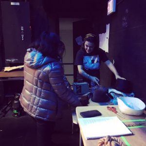 Assistant Stage Manager Risa looks over the prop table with crew members Britanie and Ha.