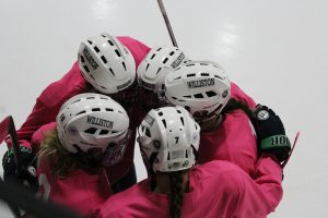 Girls varsity hockey players during its pink in the rink game