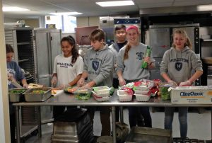 Members of the Community Service Club prepare food at Kate's Kitchen, which serves neighbors in need.