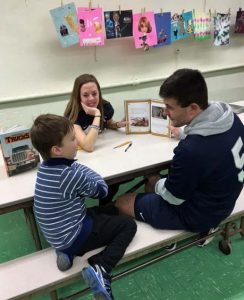 Williston student athletes discuss literature with an elementary school student.